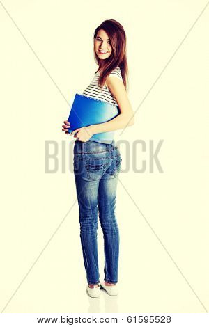 Back view of a full lenght young happy female caucasian student holding a notebook and smiling to the camera