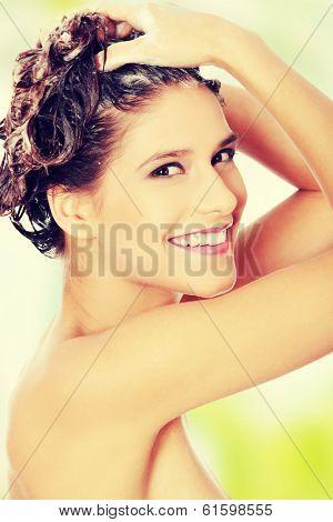 Beautiful  young woman washing her hair with shampoo