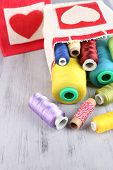 pic of lurex  - Bags with bobbins of colorful thread and woolen balls on wooden background - JPG