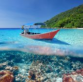 Beautiful beach and motor boat with coral reef bottom underwater and above water split view