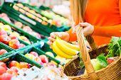 stock photo of supermarket  - Woman in supermarket at the fruit shelf shopping for groceries - JPG