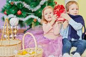 Little girl and boy sit on furry rug under christmas tree holding one red gift box together poster