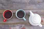 stock photo of crockery  - Tea for two with two ceramic cups of freshly brewed black tea standing on a weathered rustic wooden table alongside a teapot overhead view with copyspace - JPG