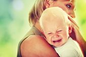 image of crying boy  - Mother holding her crying baby - JPG