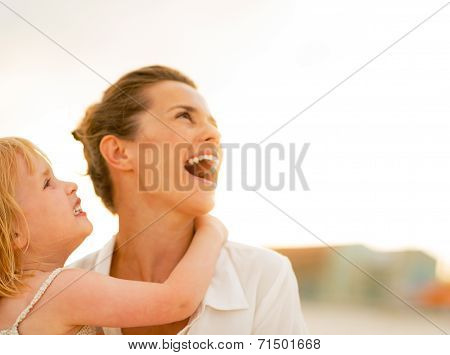 Happy Mother And Baby Girl Looking On Copy Space While On The Be