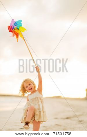 Happy Baby Girl Playing With Colorful Windmill Toy On The Beach In The Evening