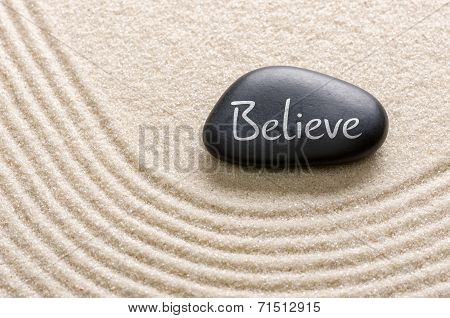 A black stone with the inscription Believe
