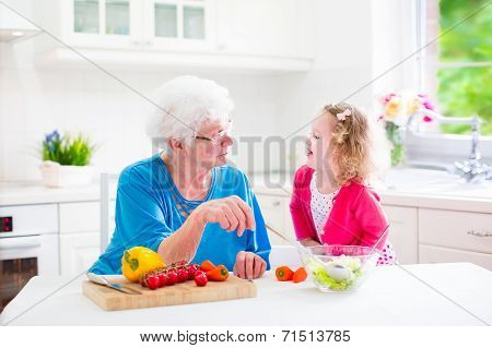 Grandmother And Little Girl Making Salad