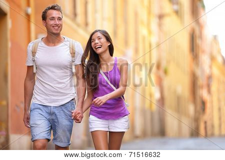 Casual young couple holding hands walking in Rome, Italy, Europe. Multiracial couple in love having fun laughing together. Asian woman, Caucasian man.