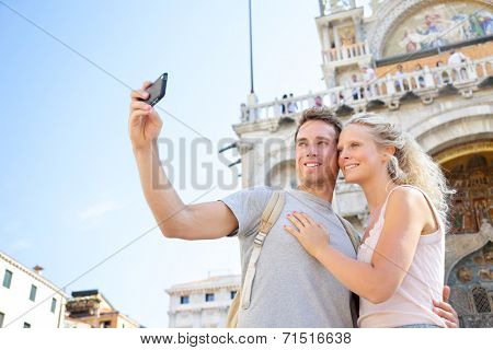 Couple on travel taking selfie photo Venice, Italy on Piazza San Marco in front of Saint Mark's Basilica. Happy young couple on vacation in Europe. Happy woman and man in love traveling together.