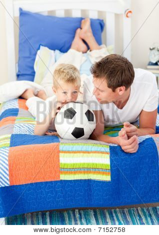 Adorable Little Boy And His Father Watching A Football Match