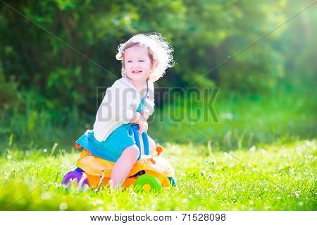 Happy Toddler Girl With Toy Car In A Garden