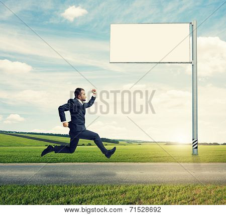 serious businessman in suit running fast on the road with empty white billboard