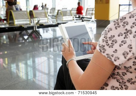 Digital tablet or e-reader at the departure gate of an airport