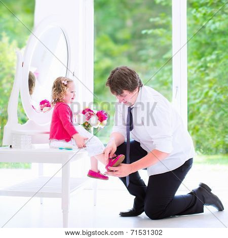 Father Helping His Daughter To Put On A Shoe