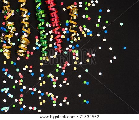 Colorful Streamer And Confetti On Black Paper