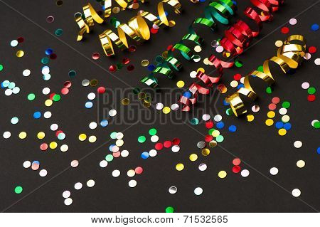 Colorful Streamer And Confetti On Black Paper Background
