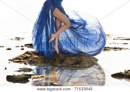 Long blue dressed slim woman legs at the beach