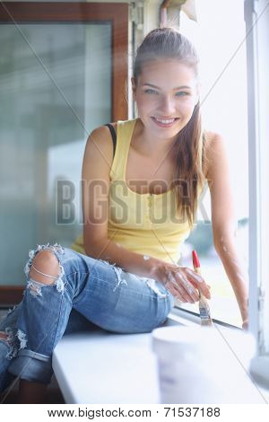 Woman painting wall of an apartment with a paintbrush carefully finishing off around  window frame