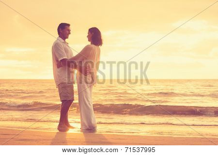 Romantic Retired Couple Relaxing on Beach Vacation at Sunset