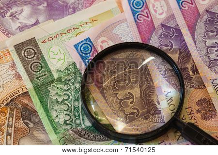 Polish Zloty Banknotes Currency And Magnifying Glass