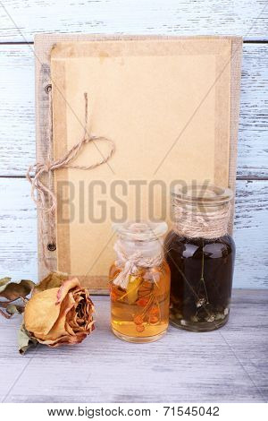 Bottles of herbal tincture, book and dried rose on wooden background