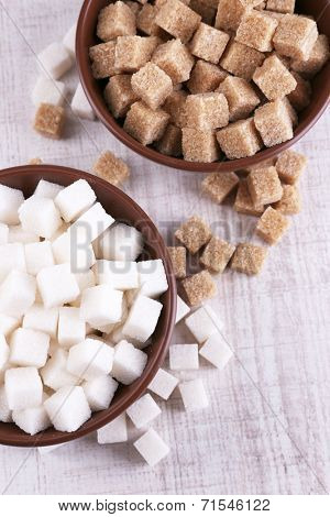 Brown and white refined sugar in color bowls on wooden background