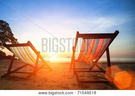 Loungers on the beach deserted oceanside at amazing sunrise.