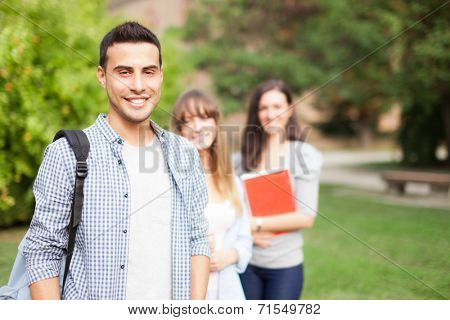 Outdoor portrait of three smiling students in a park