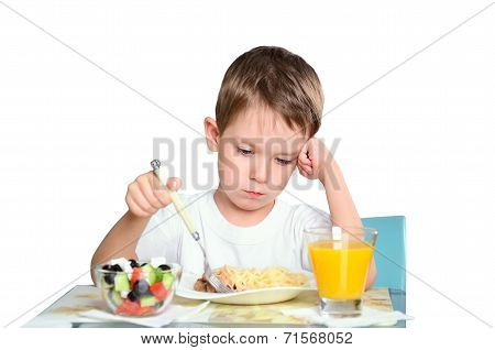 Sad Little Boy Sits At The Dining Table And Looking In The Plate. Isolated On White Background