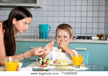 Sister Trying To Feed Her Brother. He Resists And Repels Fork With Food