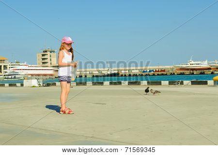 Little girl feeding pigeons on  waterfront