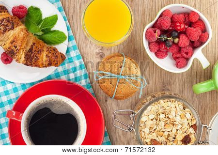 Healthy breakfast with muesli, berries, orange juice, coffee and croissant. View from above on wooden table