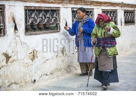 KATHMANDU, NEPAL - DEC 8, 2013: Unidentified pilgrims circle stupa Boudhanath. Stupa is one of the largest in the world, of 1979 is a UNESCO World Heritage Site.