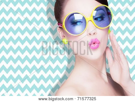 Attractive surprised young woman wearing sunglasses on zig zag background, beauty and fashion concept