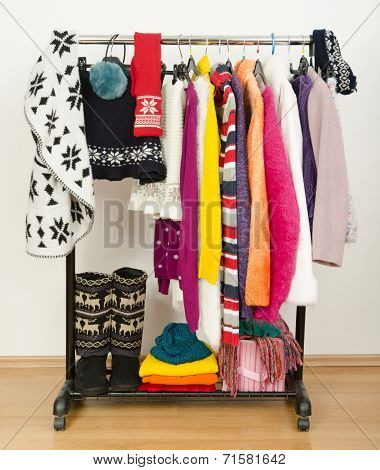 Wardrobe with winter clothes nicely arranged.