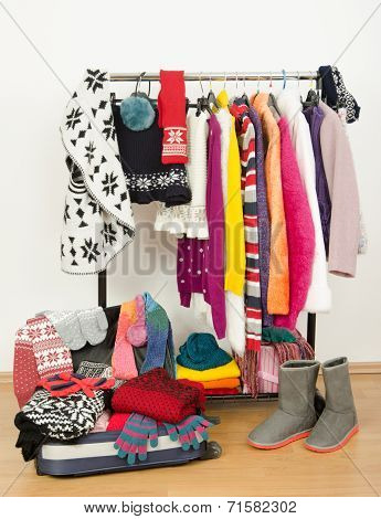 Packing the suitcase for winter vacation. Wardrobe with clothes nicely arranged and a full luggage.