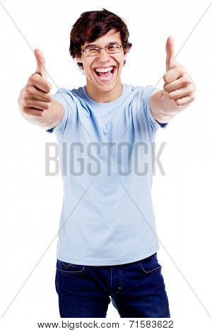 Laughing young man in glasses, blue t-shirt and jeans showing thumb up with both hands isolated on white background