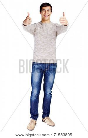 Full length portrait of smiling young man in glasses and beige sweater showing thumb up gesture with both hands isolated on white background