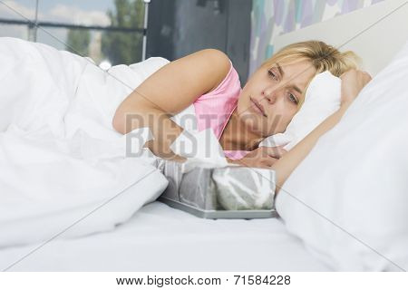 Woman suffering from cold lying with tissue box on bed