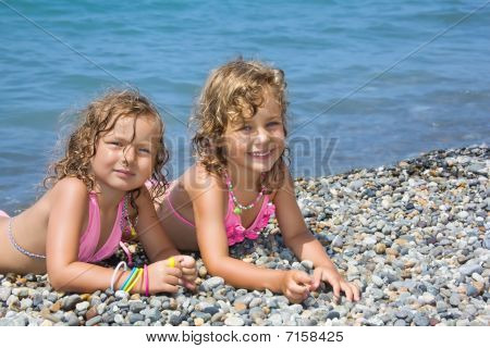 Two Pretty Little Girls Lying On Stony Beach Near Sea