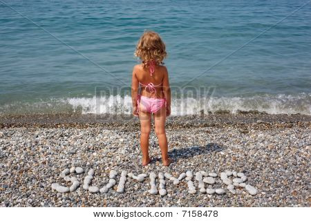 "Little girl stands on beach near water. From stones word is combined ""summer""."