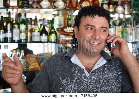 Barman talks by Smiling man against shelves with bottles.
