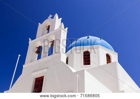A white church with blue dome in Oia or Ia on Santorini island, Greece. Traditional architecture and famous tourist attraction