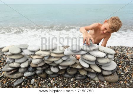 little boy is building construction of many pebbles on a sea coast