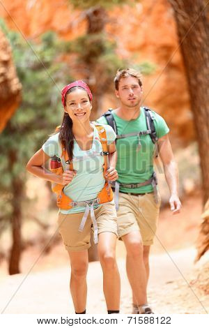 People hiking - couple hikers in Bryce Canyon walking smiling happy together. Multiracial couple, young Asian woman and Caucasian man in Bryce Canyon National Park landscape, Utah, United States.