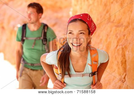 Hiking people - couple hikers in Bryce Canyon walking smiling happy together. Multiracial couple, young Asian woman and Caucasian man in Bryce Canyon National Park landscape, Utah, United States.