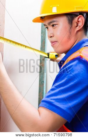 Asian Indonesian builder or craftsman with hardhat and measure tape controlling or checking a wall of a tower building or construction site