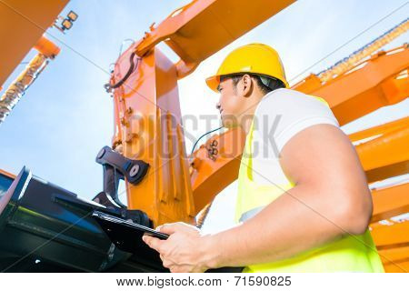Asian worker controlling construction machinery of building site or mining company