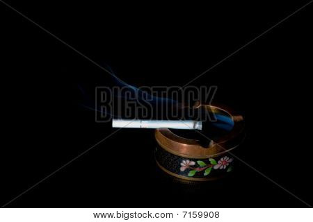 Smoking cigarette in old fancy ash-tray